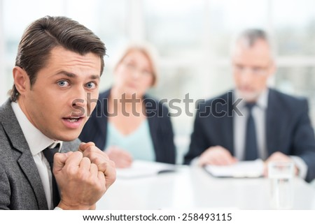 Young scared man having an interview or business meeting with employers. Office interior with big window