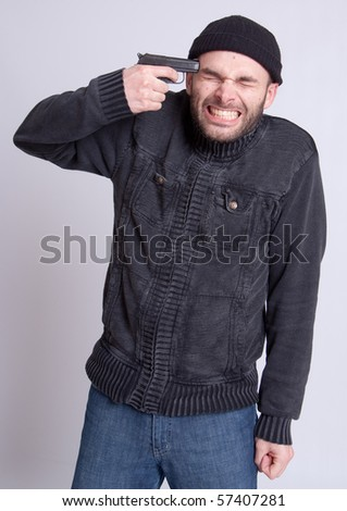 Young scared man pressing a gun to his temple - stock photo
