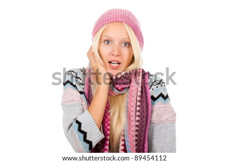 young scared, terrified woman looking at camera holding hand on face, wear winter knitted pink hat scarf and sweater, isolated over white background - stock photo