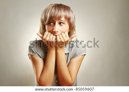 Young scared woman at desk isolated on grey - stock photo