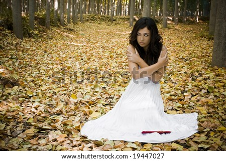 Young scared woman in dark forest. - stock photo