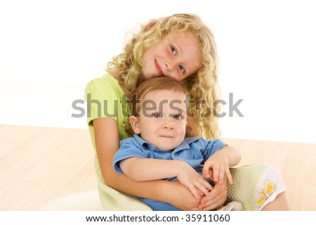 Young school age girl embraces younger brother in studio portrait - stock photo
