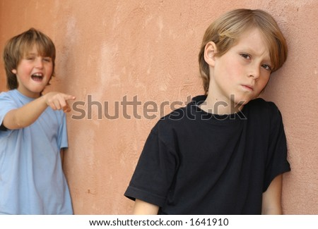 Young school boy bullying another in school playground - stock photo