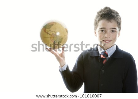 Young school boy holding a globe against a white background smiling and wearing a navy blue school uniform.