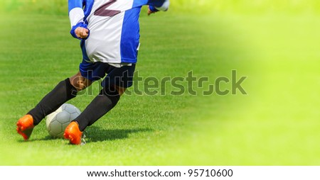 Young school child Soccer player legs dribbling in a match - stock photo