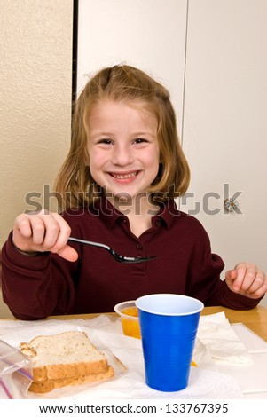 Young school girl eating lunch