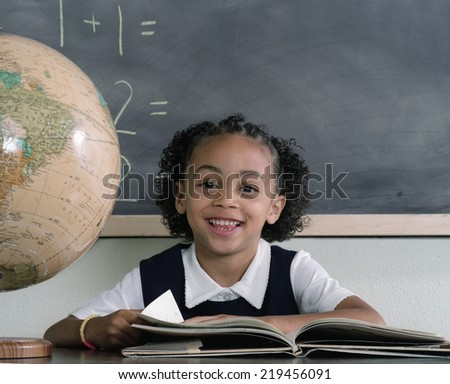 Young school girl reading at desk - stock photo