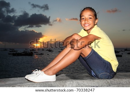 Young school girl with a big smile sitting by the sea at sunset - stock photo