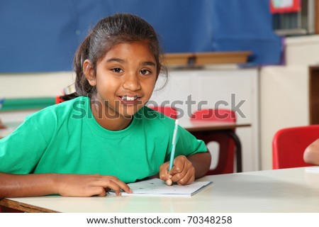 Young school girl writing at her classroom desk - stock photo