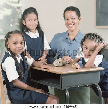 Young school girls with teacher - stock photo