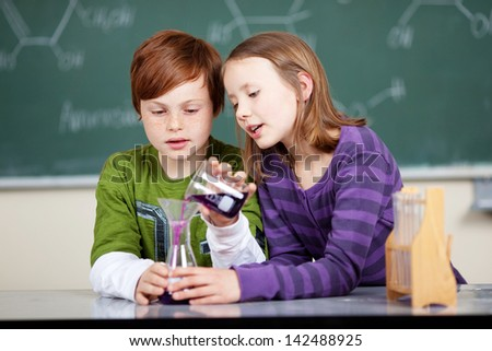 Young school kids doing a chemistry experiment with the little boy holding the flask steady while the little girl pours over a colorful liquid - stock photo