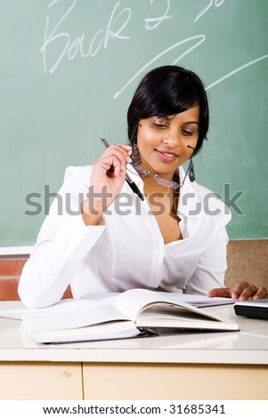 young school teacher working in the classroom - stock photo