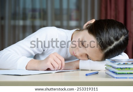 young schoolboy does his homework, she is tired and exhausted - stock photo