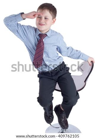 Young schoolboy in school uniform sitting an watching ahead - stock photo
