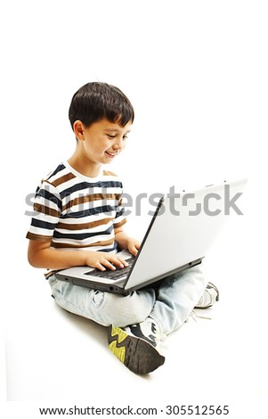 Young schoolboy is sitting on floor and surfing on his laptop. Isolated on white background - stock photo