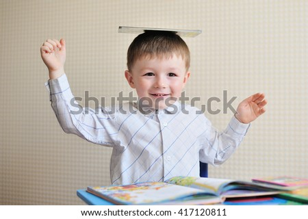 Young schoolboy playing with books and smiling as he sits at his desk in classroom - stock photo