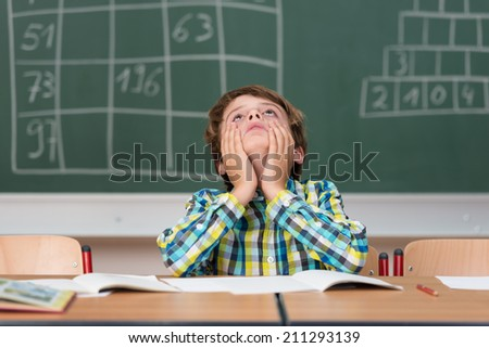 Young schoolboy searching for answers sitting at his desk in the classroom staring up into the air with a thoughtful expression - stock photo