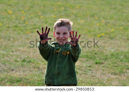 young schoolboy showing dirty hands against green blurred background, outside - stock photo