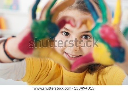 young schoolgirl hands forming a heart symbol, Selective Focus, Focus is on the Face - stock photo