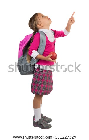 Young schoolgirl in pink school uniform and a backpack holding an apple and pointing with her finger towards something above her, isolated - stock photo