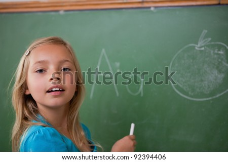 Young schoolgirl learning the alphabet on a blackboard - stock photo