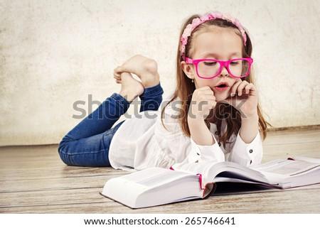 Young schoolgirl reading textbook - stock photo