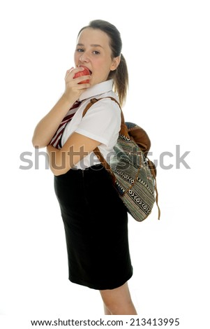 Young schoolgirl standing eating a healthy red apple with her backpack on her back standing sideways looking at the camera, on white - stock photo