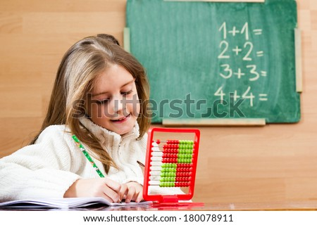 Young schoolgirl using abacus in classroom - stock photo