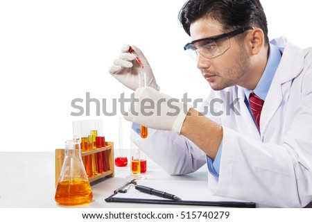 Young scientist analyzing his experiment by using chemical liquid, isolated on white background
