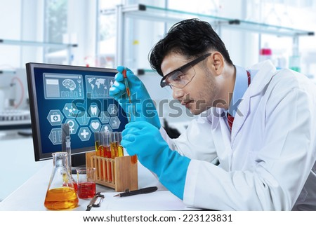 Young scientist doing research with chemistry liquid in the modern laboratory - stock photo