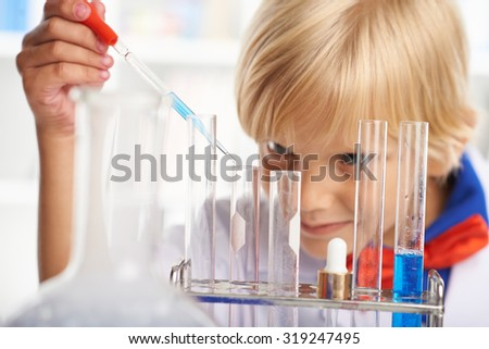 Young scientist using dropper to add blue reagent to the test-tubes