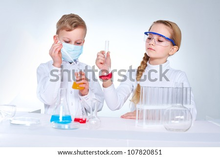 Young scientists mixing chemical substances in the lad - stock photo