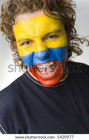 Young screaming Ecuadorian sport's fan with painted flag on face. Front view. Looking at camera - stock photo