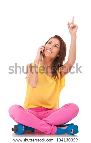 young seated casual woman talking on the phone, pointing and looking up to something - stock photo