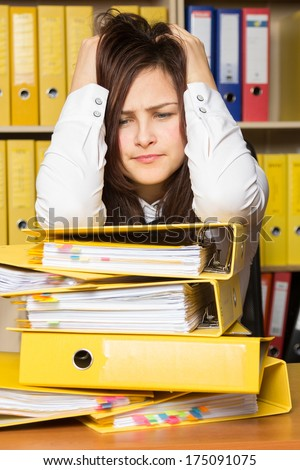 Young secretary distressed with a lot of documents on her desk - stock photo