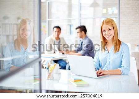 Young secretary looking at camera in working environment - stock photo