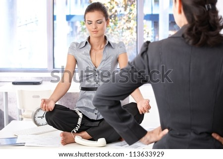 Young secretary meditating in office on top of desk, angry boss looking at her. - stock photo