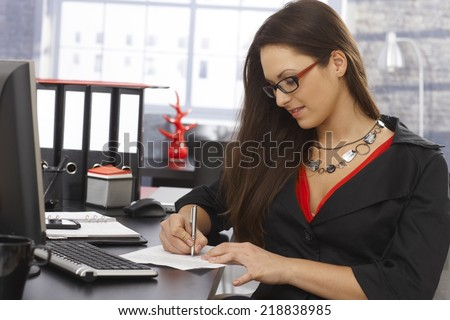 Young secretary sitting at desk in office, writing notes. - stock photo
