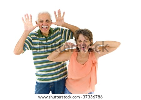 Young senior couple showing they tongue - stock photo