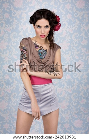 Young sensual attractive sexy european brunette woman with beautiful tattoo paint on  chest and arms posing for fashion photo shoot with red rose in her long hair in front of color floral background - stock photo