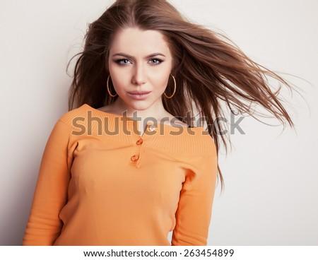 Young sensual & beauty model girl iin casual orange sweater pose in studio. - stock photo