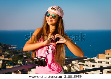 Young sensual brunette teenager girl posing on the roof in swag hat,pink trendy t-shirt and blue sunglasses, holding retro camera, doing heart shape with hands ,bright colors evening sunset sunlight - stock photo