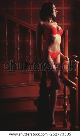 Young sensual brunette woman wearing  lingerie posing on stair - stock photo