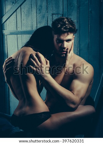 Young sensual couple of muscular macho man with bare torso and pretty sexy topless woman with back sitting on lover indoor on wooden background, vertical picture - stock photo