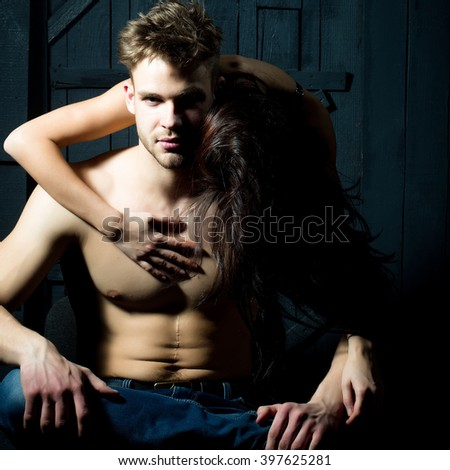 Young sensual couple of sexy muscular macho man with bare torso and pretty topless woman embracing lover indoor on wooden background, vertical picture - stock photo