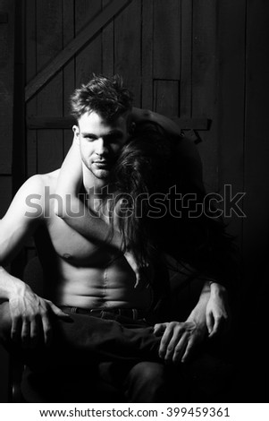 Young sensual couple of sexy muscular macho man with bare torso and pretty topless woman embracing lover indoor on wooden background black and white, vertical picture - stock photo