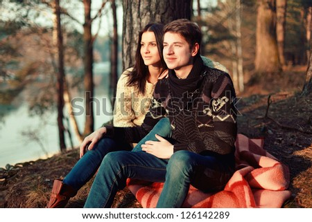 Young sensual couple sitting on the ground in park. - stock photo
