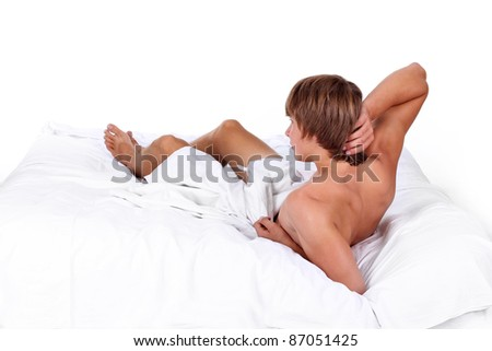Young sensual man lying on white bed, happy morning - stock photo