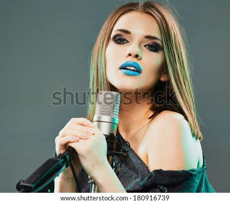 Young sensual model singing into a microphone. Beauty woman portrait.