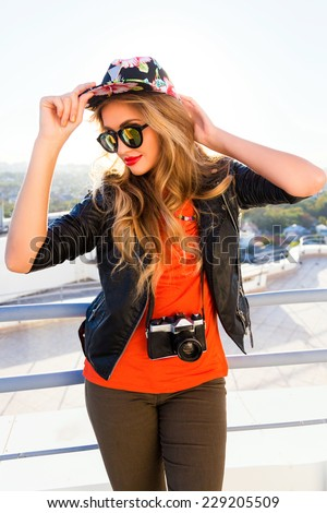 Young sensual sexy girl posing on the roof in swag hat and sunglasses, wearing leather biker jacket and holding retro camera, bright colors evening sunlight.